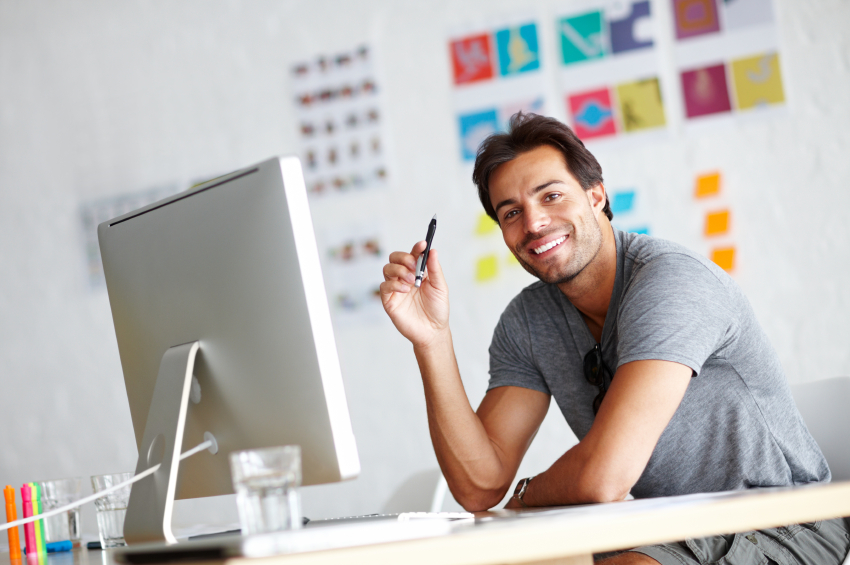 A handsome young man sitting in front of his computer while looking at the camera